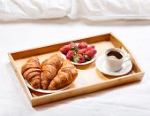 picture of bed breakfast  - breakfast in bed with coffee croissants and strawberries - JPG