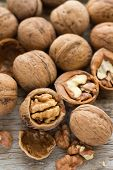 stock photo of walnut  - Walnut kernels and whole walnuts on rustic old wooden table - JPG