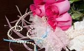 pic of garter  - Beautiful pink roses pearl beads and white stockings with garter lying on a table - JPG