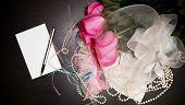 foto of garter  - Beautiful pink roses pearl beads and garter lie on a table near the note - JPG