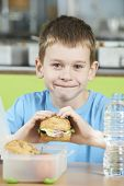 picture of school lunch  - Male Pupil Sitting At Table In School Cafeteria Eating Healthy Packed Lunch - JPG