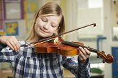 foto of violin  - Girl Learning To Play Violin In School Music Lesson - JPG