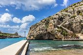 pic of gozo  - the rugged coastline of the island of Gozo are reflected in a blue sea - JPG