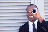 image of spyglass  - concept of black man searching thru paper spyglass - JPG