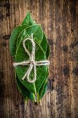 image of bay leaf  - bunch of fresh bay leaves on a rustic wooden background - JPG