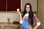 stock photo of overalls  - Brunette housewife wearing in blue denim overalls holding a piece of apple - JPG