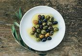 picture of olive branch  - A plate of Mediterranean olives in olive oil with a branch of olive tree over a rough old wooden desk - JPG