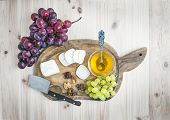 picture of brie cheese  - Goat brie cheese with fresh grapes and honey on a rustic wooden board over a light wood background - JPG