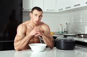stock photo of pinafore  - Man in the kitchen is going to cook - JPG