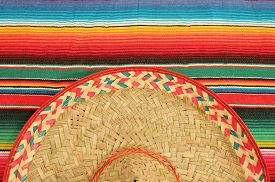 image of mexican fiesta  - fiesta mexican poncho rug in bright colors with sombrero background with copy space cinco de mayo - JPG