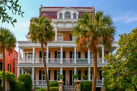 stock photo of mansion  - A stately Charleston, South Carolina mansion, with two palmetto trees in front. ** Note: Shallow depth of field - JPG