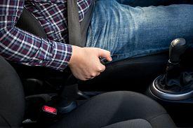 foto of levers  - Closeup of young man pulling handbrake lever in car  - JPG