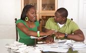 Young Ethnic Couple By Table Overwhelmed By Bills