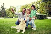 family, pet, animal, technology and people concept - happy family with labrador retriever dog taking poster