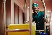 Portrait of smiling African bellhop helping guests, pushing luggage cart delivering bags to hotel ro poster