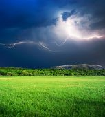 stock photo of lightning bolts  - Thunderstorm with lightning  in green meadow - JPG