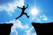 stock photo of leaping  - Man jump through the gap - JPG
