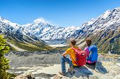 Backpackers couple hiking looking at Mt Cook view on mountains tramping in New Zealand. People hiker poster