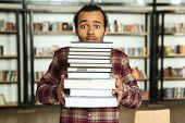 Image of young confused african man student standing in library with a lot of books. Looking at came poster