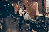 Barber Shop Classy Dressed Specialist Is Styling The Hair Of A Client. Salon Is Retro And Vintage. C poster