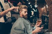 Chill Out At The Barber Shop. Side View Of Handsome Young Red Bearded Man Drinking Scotch And Browsi poster