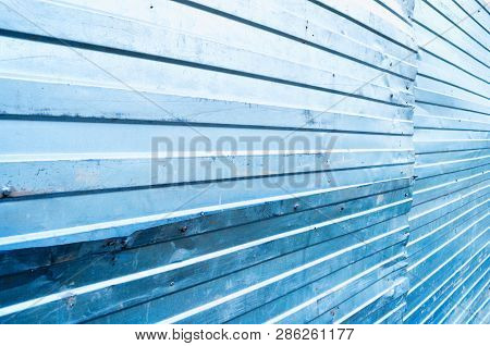 poster of Industrial metallic background. Corrugated zinc metal texture, metal fence closeup view. Metal background