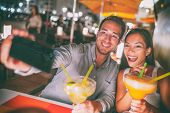 Fun date night out young people taking selfie of themselves drinking giant margaritas cocktails part poster