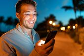 Man smiling looking at phone outside on city street at night texing online using smartphone. Young m poster