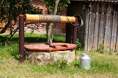 foto of water well  - vintage water well and milk canister in the countryside - JPG