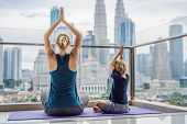 Mom And Son Are Practicing Yoga On The Balcony In The Background Of A Big City. Sports Mom With Kid  poster