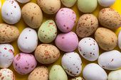 Multicolored Speckled Chocolate Eggs Arranged In Pattern On Bright Yellow Background. Easter Card Po poster