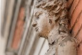 Old White Caryatid Made Of Concrete In An Old Brick House. The Sculpture Cracks. poster