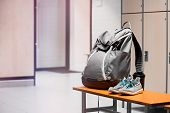 Sports Shoes, Sport Backpack And Sport Water Bottle In Gym Locker Room. poster