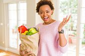 Young african american woman holding paper bag full of fresh groceries very happy and excited, winne poster