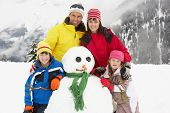 Family Building Snowman On Ski Holiday In Mountains