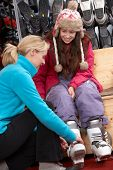stock photo of ski boots  - Sales Assistant Helping Teenage Girl To Try On Ski Boots In Hire Shop - JPG