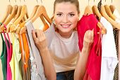 image of department store  - beautiful young woman near rack with hangers - JPG