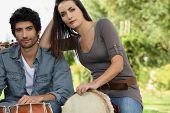 pic of bongo  - Couple playing bongo drums outdoors - JPG