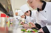 foto of supervision  - Chef finishing her salad in culinary class in kitchen - JPG