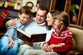 Portrait of friendly family reading book on Christmas evening