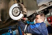stock photo of auto garage  - car mechanic examining car suspension of lifted automobile at repair service station - JPG