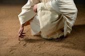 stock photo of gospel  - Jesus writing in the sand with finger - JPG