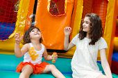 stock photo of bouncing  - Two cute young sisters playing with bubble wand at the bouncing castle on the background - JPG