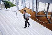 Elevated view of young businessman running upstairs in office lobby