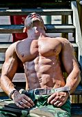 foto of bulge  - Handsome muscular bodybuilder laying on wood stairs in the sun showing bulging pecs and abs - JPG