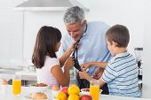 Children fixing their fathers tie in the kitchen at home