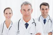 stock photo of tunic  - Cheerful doctors posing together crossing arms in bright office - JPG