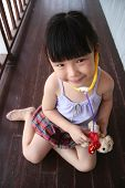 Girl Playing Stethoscope On Toy Puppy poster