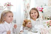 image of little sister  - Two little cute sisters playing at tea parties - JPG
