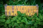 stock photo of playgroup  - Rustic Sign In The Garden Of A Rural School Playgroup - JPG